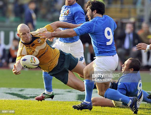 Australia's centre and captain Stirling Mortlock sends the ball as he is tackled by Italy's Sergio Parisse and Italy's scrumhalf Pablo Canavosio...