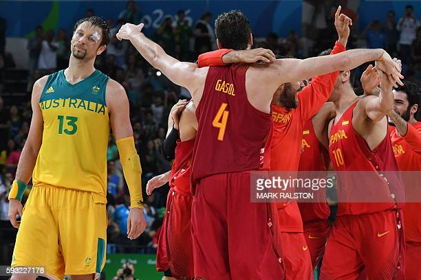Australia's centre David Andersen reacts as Spain's centre Pau Gasol and teammates celebrate after winning a Men's Bronze medal basketball match...