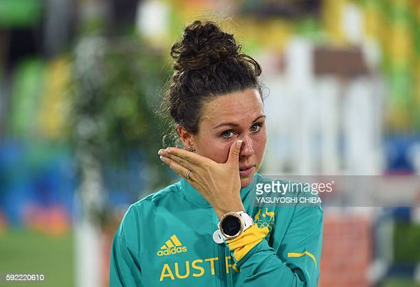 Australia's Chloe Esposito wipes her face as she waits to be awarded the gold medal in the women's modern pentathlon at the Deodoro Stadium during...