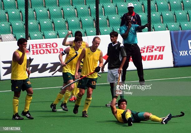 Australia's Chris Ciriello, lying on ground, celebrates with teammates after scoring a goal against Pakistan to win their men's field hockey match...