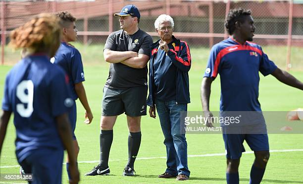 Australia's coach Ange Costecoglou and Jim Moriarty watch a group of young Aboriginal football players from Australia's Northern Territory train...