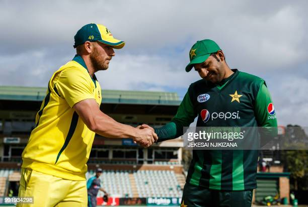 Australia's cricket captain Aaron Finch shakes hands with Pakistan's captain Sarfraz Ahmed after winning the toss ahead of the fifth T20 cricket...