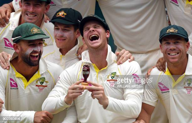 Australia's cricket team celebrates after retaining the Ashes trophy defeating England on the final day of the fifth Ashes cricket Test match at the...