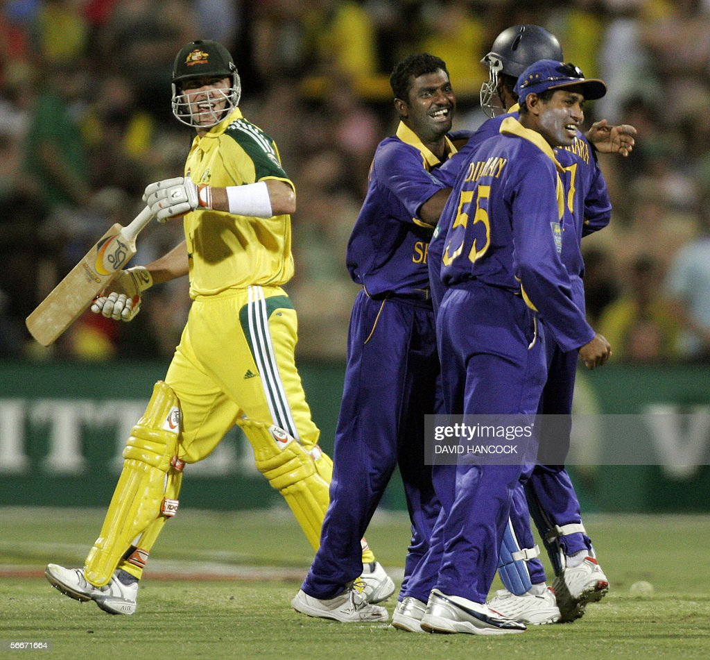 Australia's Damien Martyn (L) walks as the Sri Lankan team celebrate in a One Day International match won by Australia at the Adelaide Oval 26 January 2006. Martyn made 46 before being bowled by Muttiah Muralitharan but Australia won the match 5-219 beating Sri Lanka's total of 218. Australia now leads the competition on 14 points with Sri Lanka on 9 and South Africa on 8.
