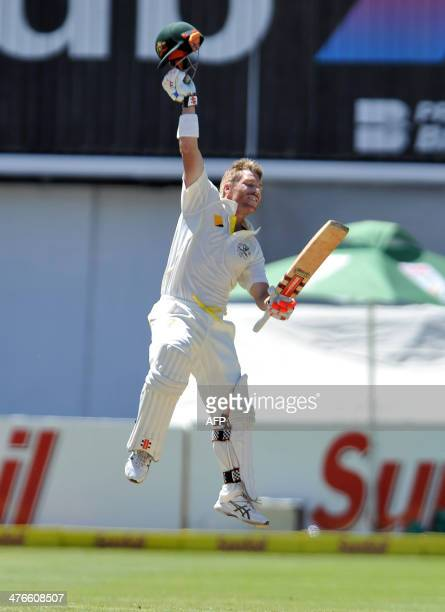 Australia's David Warner celebrates after reaching the 100 run mark on Day 4 of the third Test match between South Africa and Australia at Newlands...