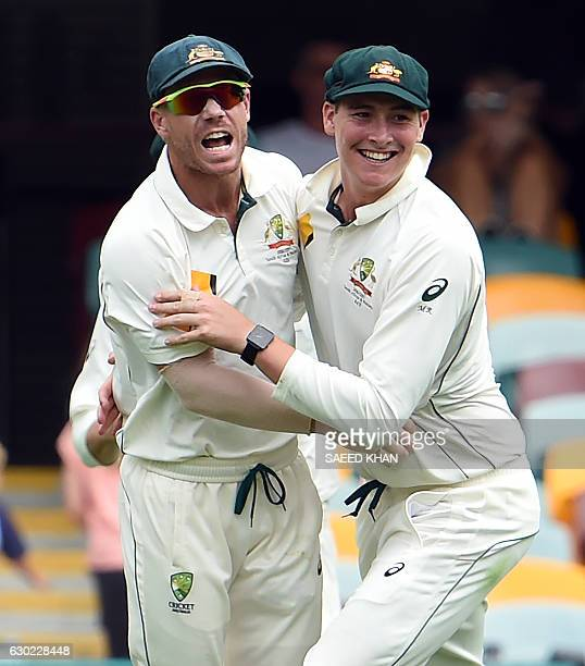 Australia's David Warner celebrates Pakistan's batsman Asad Shafiq successful catch out with teammate Matt Renshaw during the fifth day of the first...
