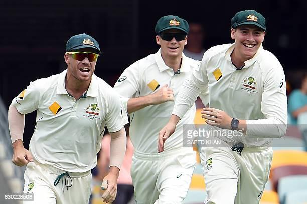 Australia's David Warner celebrates Pakistan's batsman Asad Shafiq's successful catch out with teammates Matt Renshaw and Peter Handscomb during the...