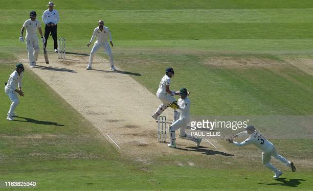 Australia's David Warner dives to catch the ball and take the wicket of England's captain Joe Root for 77 runs off the bowling of Australia's Nathan...