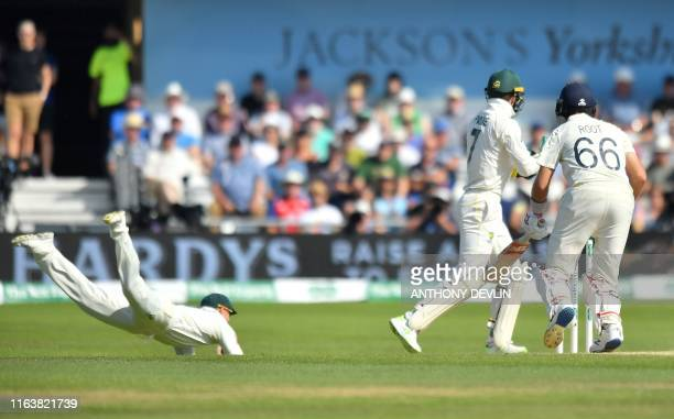 Australia's David Warner dives to catch the ball to take the wicket of England's captain Joe Root for 77 runs on the fourth day of the third Ashes...