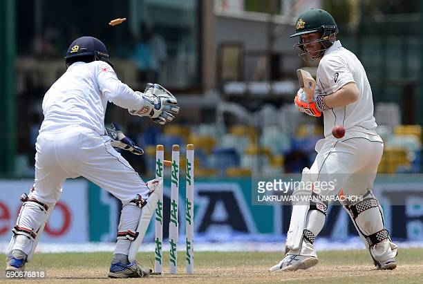 Australia's David Warner looks back to his shattered wicket after his dismissal by unseen Sri Lankan bowler Dilruwan Perera as wicketkeeper Kusal...