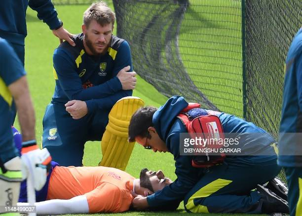 Australia's David Warner looks on as an injured net bowler receives medical attention during a training session at The Oval in London on June 8 ahead...