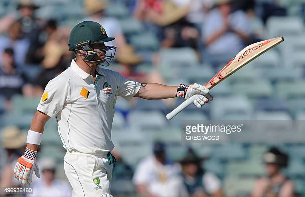 Australia's David Warner raises his bat after reaching 150 runs on the first day of the second Test cricket match between Australia and New Zealand...