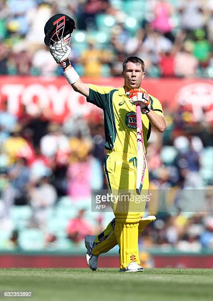 Australia's David Warner raises his bat and helmet as he celebrates after scoring a century during the fourth oneday international cricket match...