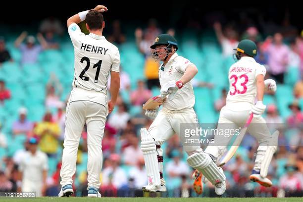 Australias David Warner runs between the wickets as New Zealand's Matt Henry looks on during the fourth day of the third cricket Test match between...