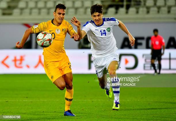 Australia's defender Trent Sainsbury vies for theball with Uzbekistan's forward Eldor Shomurodov during the 2019 AFC Asian Cup Round of 16 football...