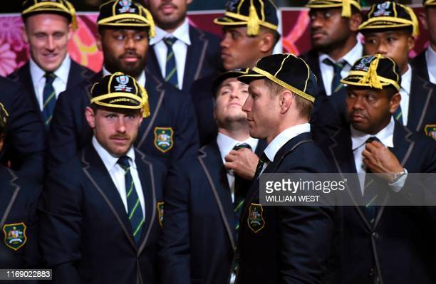 Australia's flanker David Pocock walks past teammates before a team photo during a welcoming ceremony at Ebetsu, Hokkaido Prefecture, on September 18...