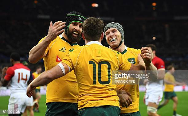 Australia's fly half Quade Cooper is congratulated by teammates after scoring a try during the rugby union test match between France and Australia at...