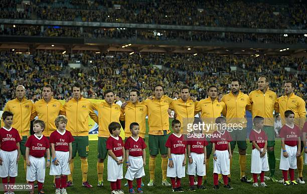 Australia's football players listen to the national anthem prior to their match against Iraq during their 2014 World Cup qualifier in Sydney on June...