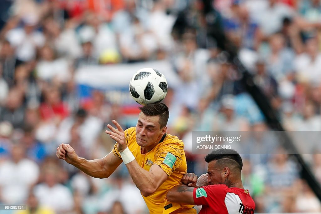 TOPSHOT - Australia's forward Tomi Juric (L) jumps for the ball with Peru's defender Miguel Trauco during the Russia 2018 World Cup Group C football match between Australia and Peru at the Fisht Stadium in Sochi on June 26, 2018. (Photo by Adrian DENNIS / AFP) / RESTRICTED
