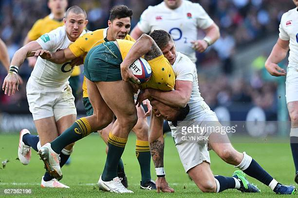 Australia's fullback Israel Folau is tackled by England's centre Owen Farrell during the international rugby union test match between England and...