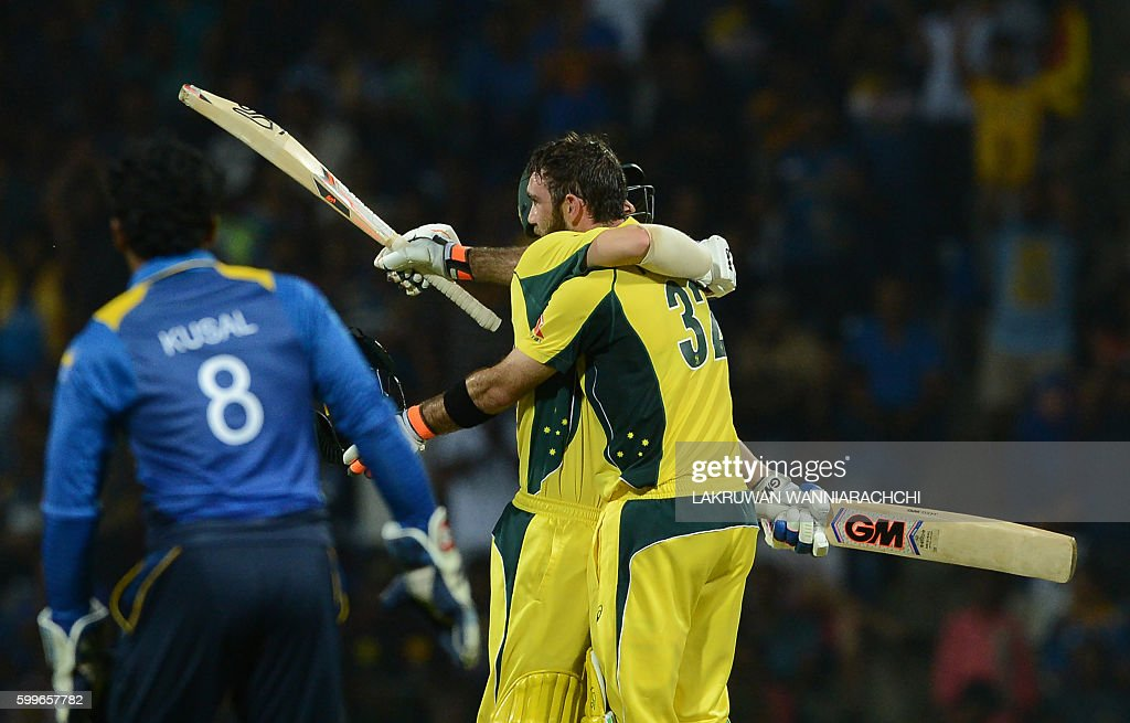 Australia's Glenn Maxwell (R) is congratulated by his teammate Travis Head (C) after scoring a century (100 runs) during the first T20 international cricket match between Sri Lanka and Australia at the Pallekele International Cricket Stadium in Pallekele on September 6, 2016. / AFP / LAKRUWAN