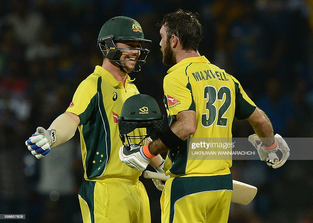Australia's Glenn Maxwell (R) is congratulated by his teammate Travis Head (L) after scoring a century (100 runs) during the first T20 international cricket match between Sri Lanka and Australia at the Pallekele International Cricket Stadium in Pallekele on September 6, 2016. / AFP / LAKRUWAN