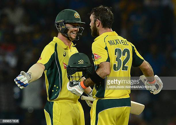 Australia's Glenn Maxwell is congratulated by his teammate Travis Head after scoring a century during the first T20 international cricket match...