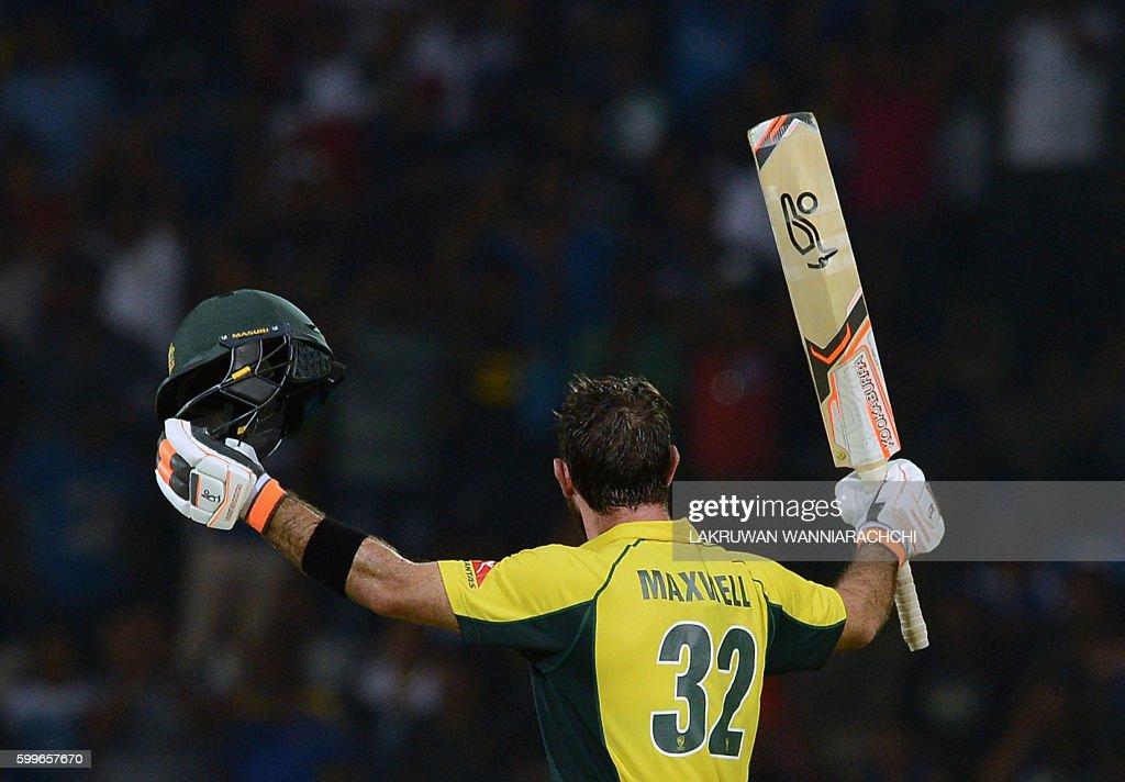 Australia's Glenn Maxwell raises his bat and helmet in celebration after scoring a century (100 runs) during the first T20 international cricket match between Sri Lanka and Australia at the Pallekele International Cricket Stadium in Pallekele on September 6, 2016. / AFP / LAKRUWAN