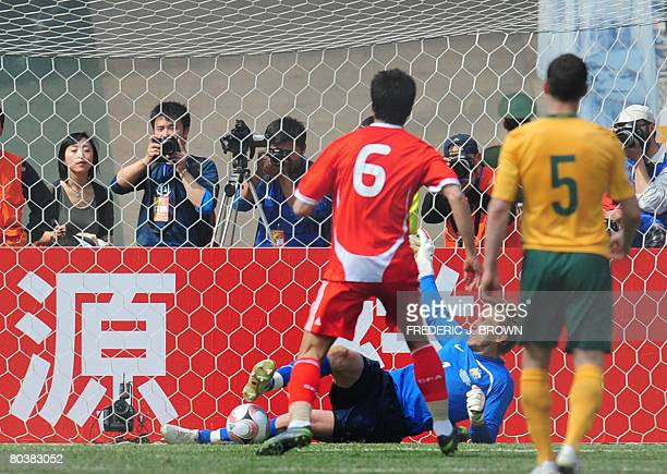 Australia's goalkeeper Mark Schwarzer saves a penalty late in the game from China's Shao Jiayi as Jason Culina watches during their 2010 World Cup...