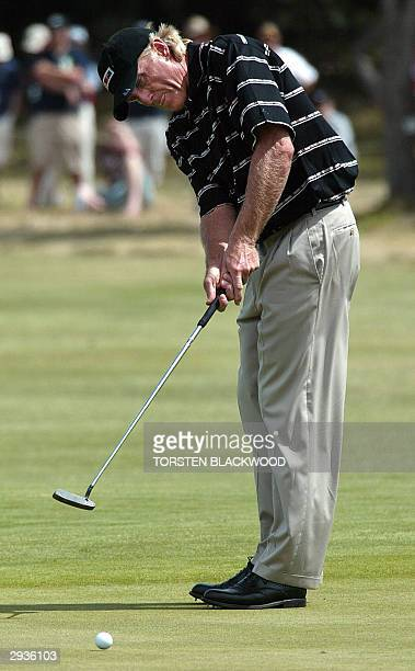 Australia's Greg Norman ranked 220th in the world bites his tongue as he watches his putt on the 9th green during the second round of the Heineken...