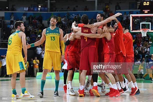 Australia's guard Matthew Dellavedova and Australia's centre David Andersen react as Spain's players celebrate winning the Men's Bronze medal...