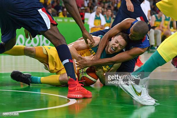 Australia's guard Matthew Dellavedova falls along with France's point guard Tony Parker during a Men's round Group A basketball match between...