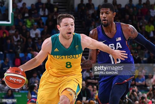 Australia's guard Matthew Dellavedova holds off USA's guard Paul George during a Men's round Group A basketball match between Australia and USA at...