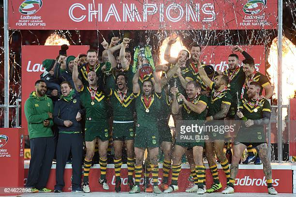 Australia's hooker and captain Cameron Smith holds the trophy after winnging the rugby league Four Nations Final match between Australia and New...