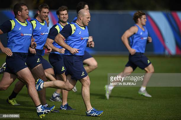 Australia's hooker and captain Stephen Moore runs with teammates during a team training session in Teddington west London on October 27 2015 during...