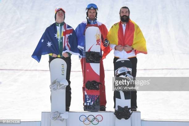 Australia's Jarryd Hughes France's Pierre Vaultier and Spain's Regino Hernandez celebrate on the podium after the men's snowboard cross big final at...