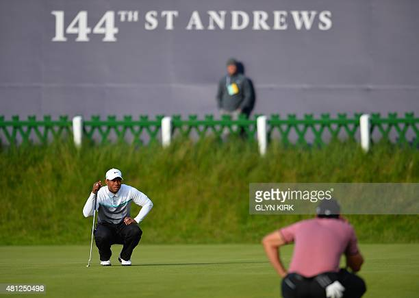 Australia's Jason Day and US golfer Tiger Woods line up putts on the 18th green during the completion of their second rounds on day three of the 2015...
