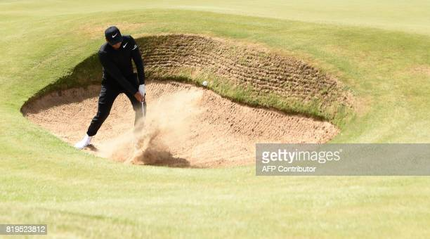TOPSHOT Australia's Jason Day plays out of a greenside bunker on the 7th hole during his opening round on the first day of the Open Golf Championship...