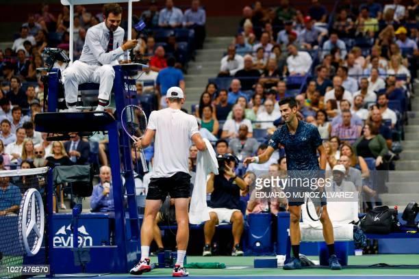 Australia's John Millman and Serbia's Novak Djokovic speak to the umpire during their Men's Singles QuarterFinals match at the 2018 US Open at the...