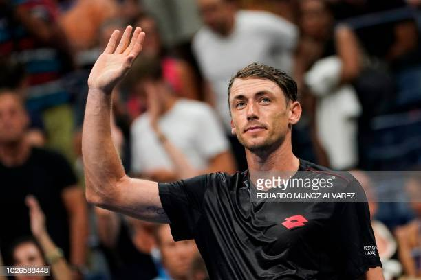 Australia's John Millman celebrates after defeating Switzerland's Roger Federer during their 2018 US Open Men's Singles tennis match at the USTA...