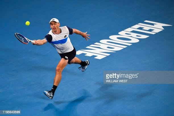 Australia's John Millman hits a return against Switzerland's Roger Federer during their men's singles match on day five of the Australian Open tennis...