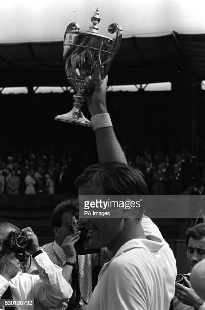 Australia's John Newcombe the new men's singles champion holding aloft his trophy which he received from Princess Marina president of the AllEngland...