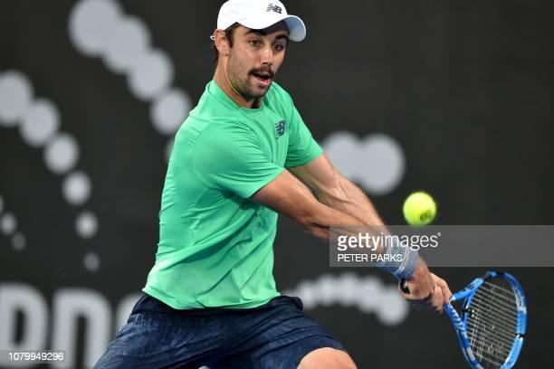 Australia's Jordan Thompson hits a return against his compatriot Alex De Minaur during their men's singles quarterfinal match at the Sydney...