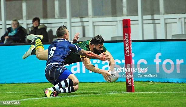 Australia's Josh Mansour scores his sides sixth try under pressure from Scotland's Danny Brough during the Four Nations match between the Australian...