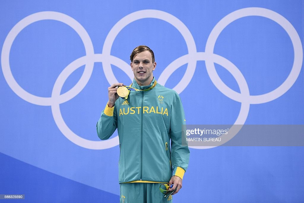 Australia's Kyle Chalmers poses with his gold medal on the podium of the Men's 100m Freestyle Final during the swimming event at the Rio 2016 Olympic Games at the Olympic Aquatics Stadium in Rio de Janeiro on August 10, 2016. / AFP / Martin BUREAU