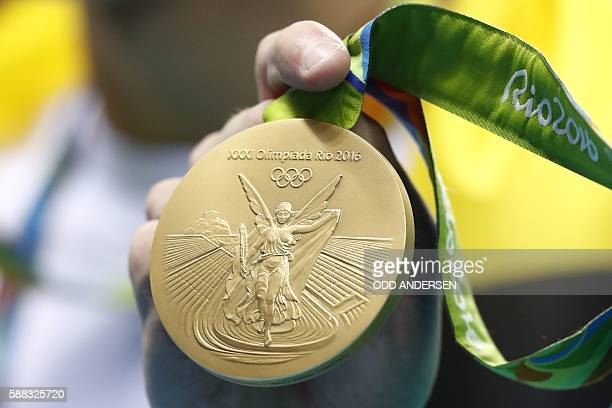 TOPSHOT Australia's Kyle Chalmers poses with his gold medal on the podium of the Men's 100m Freestyle Final during the swimming event at the Rio 2016...