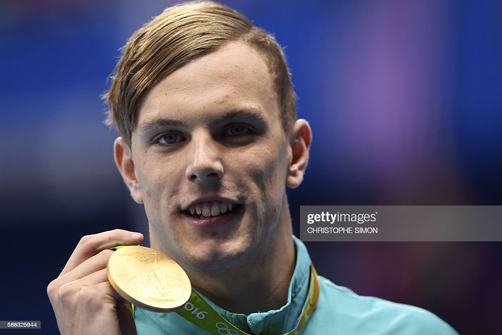 Australia's Kyle Chalmers poses with his gold medal on the podium of the Men's 100m Freestyle Final during the swimming event at the Rio 2016 Olympic Games at the Olympic Aquatics Stadium in Rio de Janeiro on August 10, 2016. / AFP / CHRISTOPHE