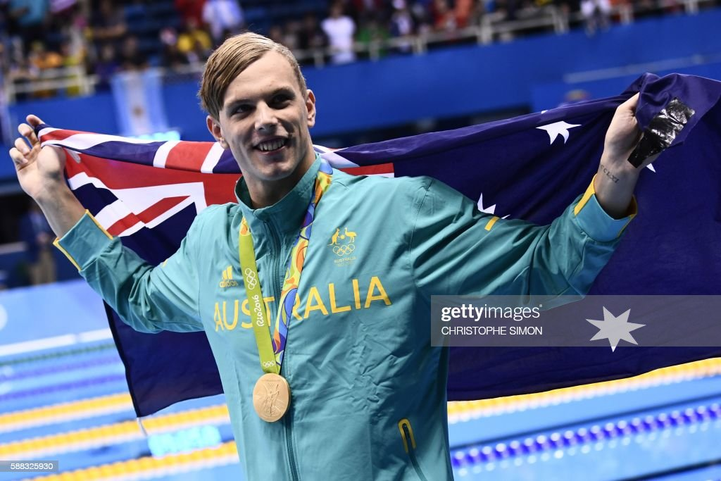 Australia's Kyle Chalmers waves his national flag during the medal ceremony of the Men's 100m Freestyle Final during the swimming event at the Rio 2016 Olympic Games at the Olympic Aquatics Stadium in Rio de Janeiro on August 10, 2016. /