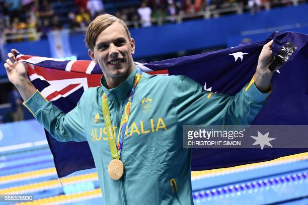 Australia's Kyle Chalmers waves his national flag during the medal ceremony of the Men's 100m Freestyle Final during the swimming event at the Rio...