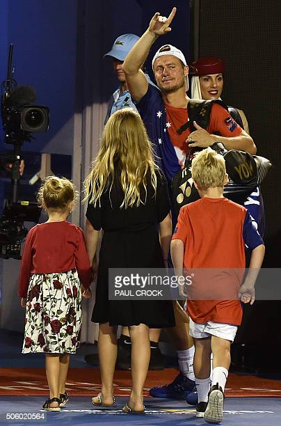 Australia's Lleyton Hewitt gestures as he walks off court with family members after defeat in his men's singles match against Spain's David Ferrer on...